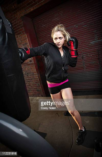 A teenage girl punches a punching bag while training for mixed martial arts outside a warehouse in Birmingham, Alabama.