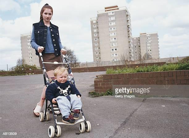 Teenage girl (16-18) pushing male toddler (12-15 months) in stroller