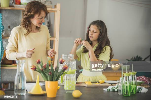 teenage girl putting mint into lemonade she is preparing with her mother - mint plant family stock pictures, royalty-free photos & images