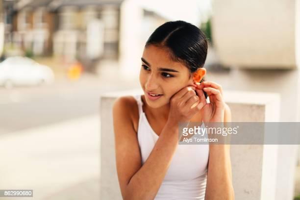 Teenage girl putting on earring