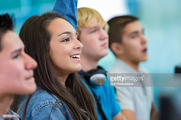 Teenage girl raising hand, asking question in high school class