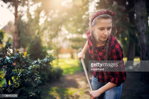 teenager-mädchen raken am sonnigen frühlingstag - haushaltsaufgabe stock-fotos und bilder