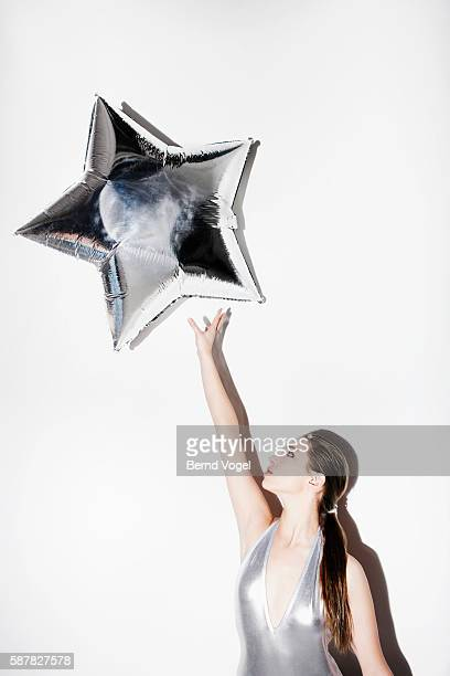 Teenage girl reaching for a star