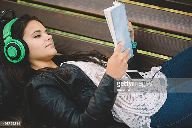 Teenage girl reading a book and listening to the music