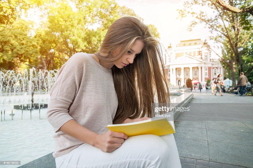 Teenage girl reading a book : Stock Photo