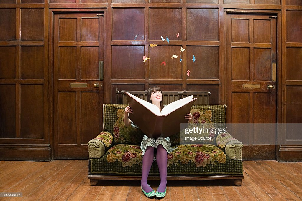 A teenage girl reading a large book : Stock Photo