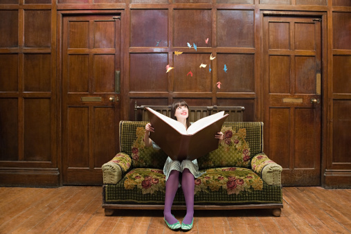 A teenage girl reading a large book - gettyimageskorea