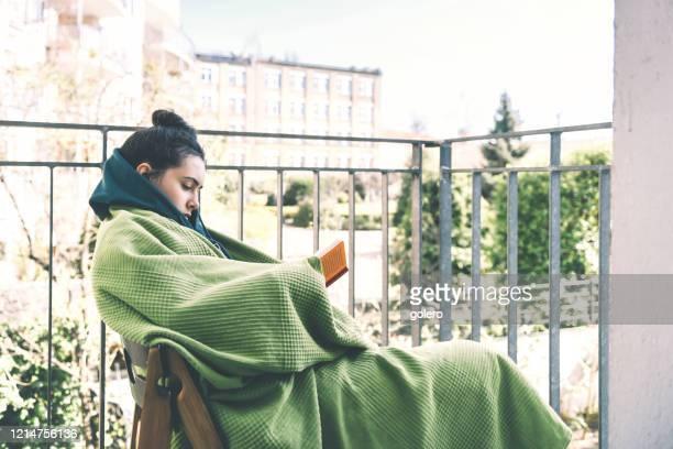 adolescente livro de leitura na varanda - lockdown - fotografias e filmes do acervo