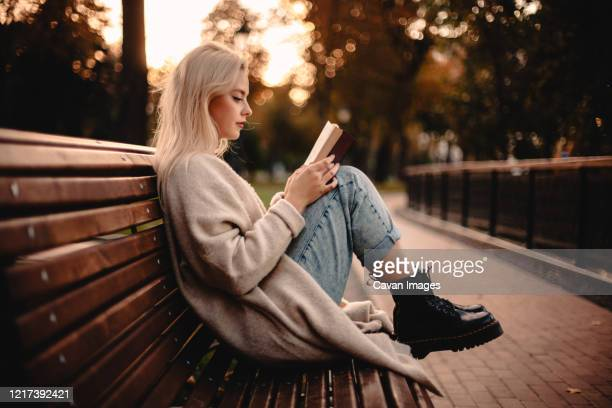 teenage girl reading book sitting on bench in park during autumn - resting ストックフォトと画像