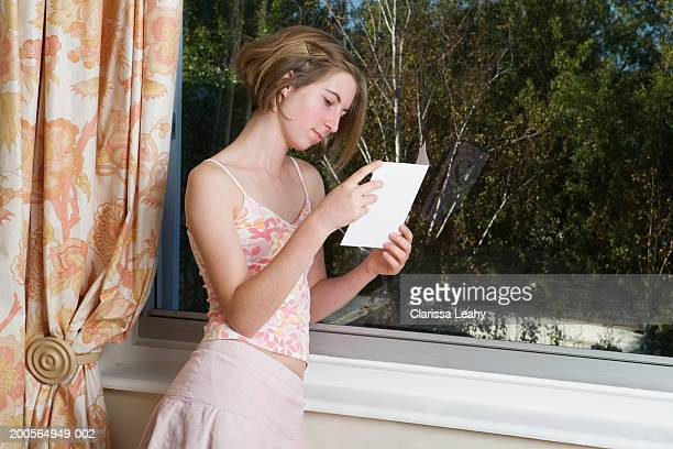 teenage girl (16-17 years) reading card, standing by window, side view - 16 17 years stock pictures, royalty-free photos & images