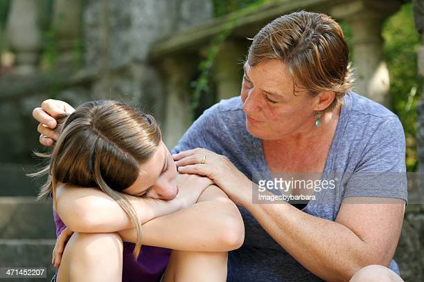 Teenage girl receiving comfort and support from mother.