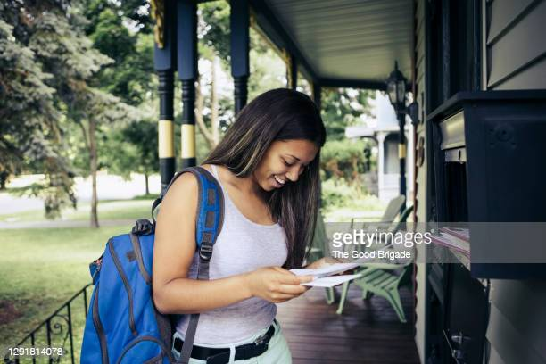 teenage girl receiving letter of acceptance for college in mail - university stock pictures, royalty-free photos & images