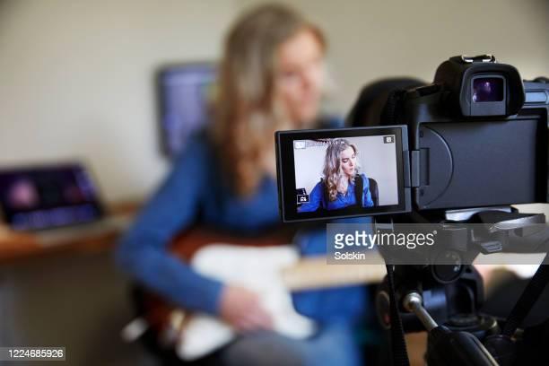 teenage girl recording herself on camera playing the guitar - digital viewfinder stockfoto's en -beelden