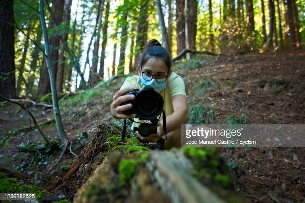 a teenage girl records a video on a fallen tree in the forest - film director stock pictures, royalty-free photos & images