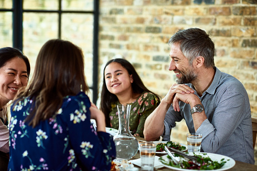 Teenage girl relaxing at dinner with her parents and their friends - gettyimageskorea