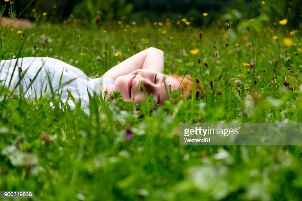 teenage girl relaxing on a meadow - graspflanze stock-fotos und bilder