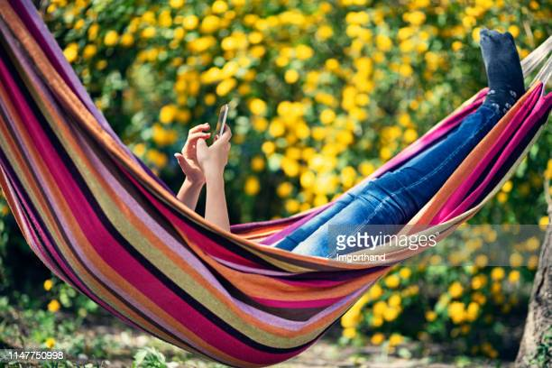 teenage girl relaxing on hammock and using smartphone - lazy poland stock photos and pictures