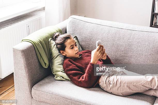 teenage girl relaxing on sofa looking at smartphone