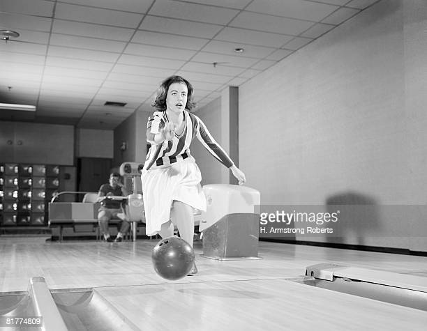 Teenage girl releasing bowling ball into alley, friend looking on in background.
