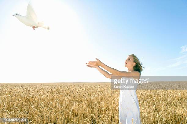 Teenage girl (13-15) releasing dove in wheat field, side view