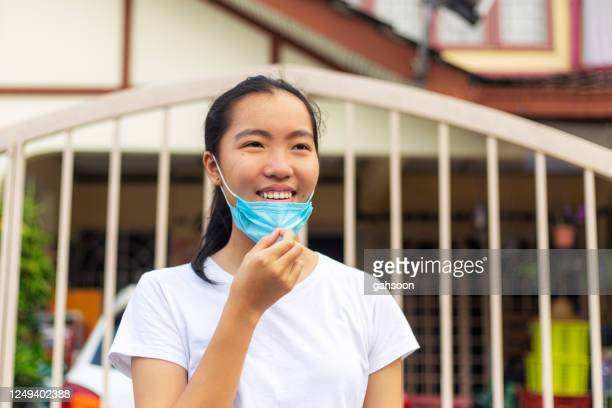 teenage girl removing facemask and smile happily, feeling relief that the lockdown situation is over - removing stock pictures, royalty-free photos & images