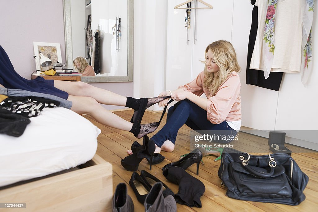 Teenage girl removing friends tights : Stock Photo