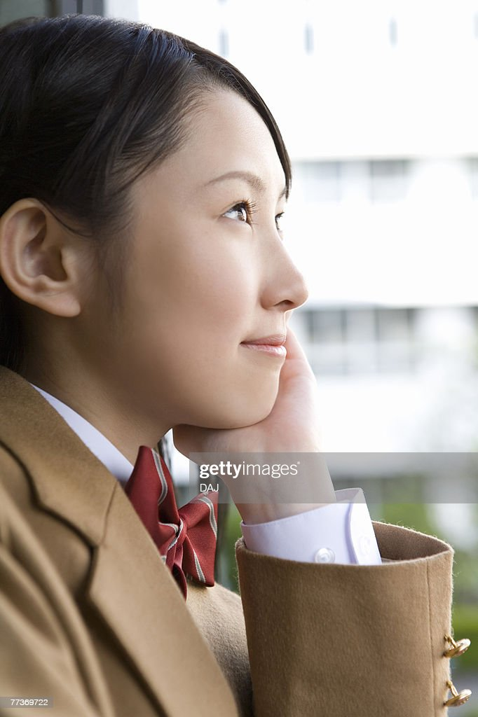 Teenage girl resting chin in hand, smiling : Photo