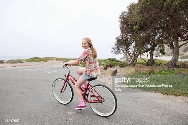 Teenage girl riding a red bike along the beach