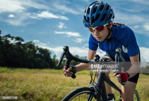 teenage girl riding bicycle by field - torwai stock pictures, royalty-free photos & images