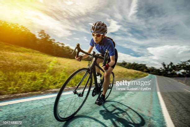 teenage girl riding bicycle on road by field - torwai stock pictures, royalty-free photos & images