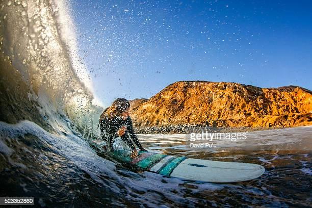 teenage girl (16-17) riding longboard through water tube on maibu coast, california, usa - malibu foto e immagini stock