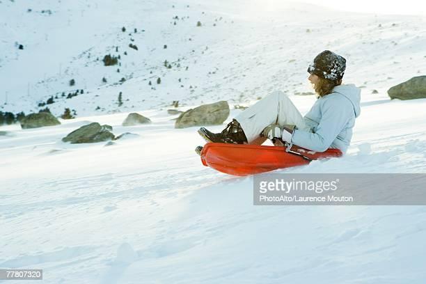Teenage girl riding sled on ski slope, side view, full length