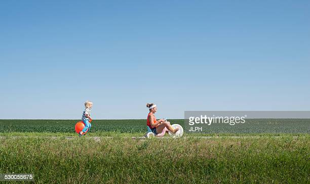 teenage girl riding tricycle and boy on inflatable hopper - hoppity horse stock photos and pictures