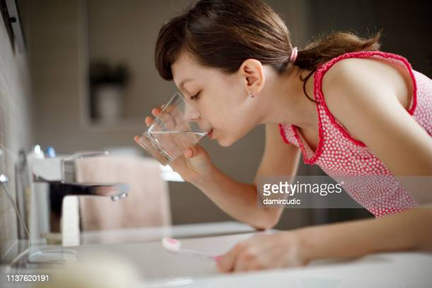 teenage girl rinsing her mouth with glass of water - mouthwash stock pictures, royalty-free photos & images