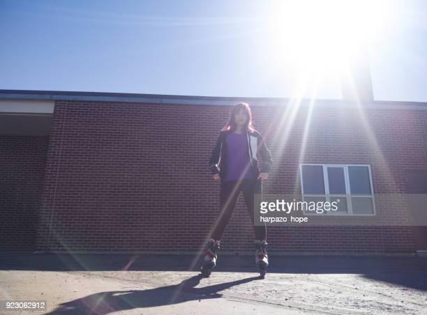 Teenage girl rollerblading by a brick building.