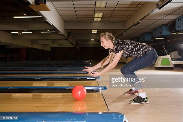 Teenage girl (15-17) rolling a bowling ball