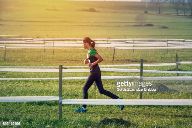 Teenage girl running in the countryside on a magical sunny day