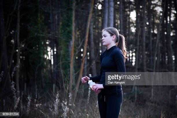 Teenage girl running in woods in winter
