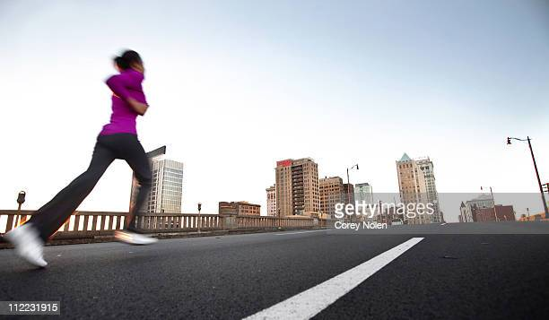 A teenage girl runs on the street away from the camera towards downtown Birmingham, Alabama. (motion blur)