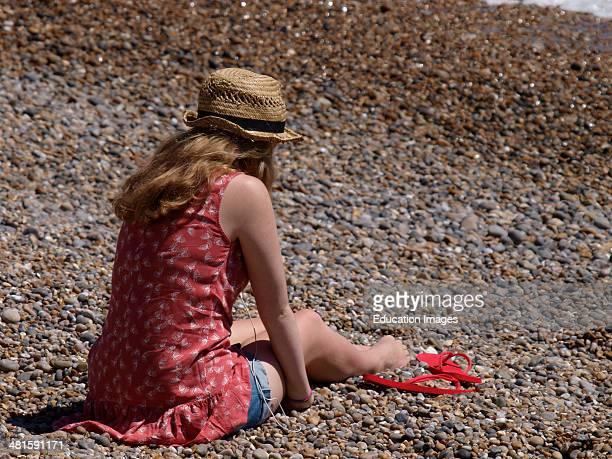 Teenage girl sat on the beach Seaton Devon UK