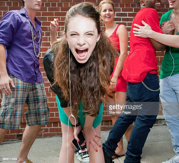 Teenage girl screaming with friends in background