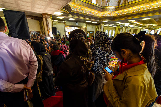 a teenage girl sends text messages on her cell phone at an iranian new year party