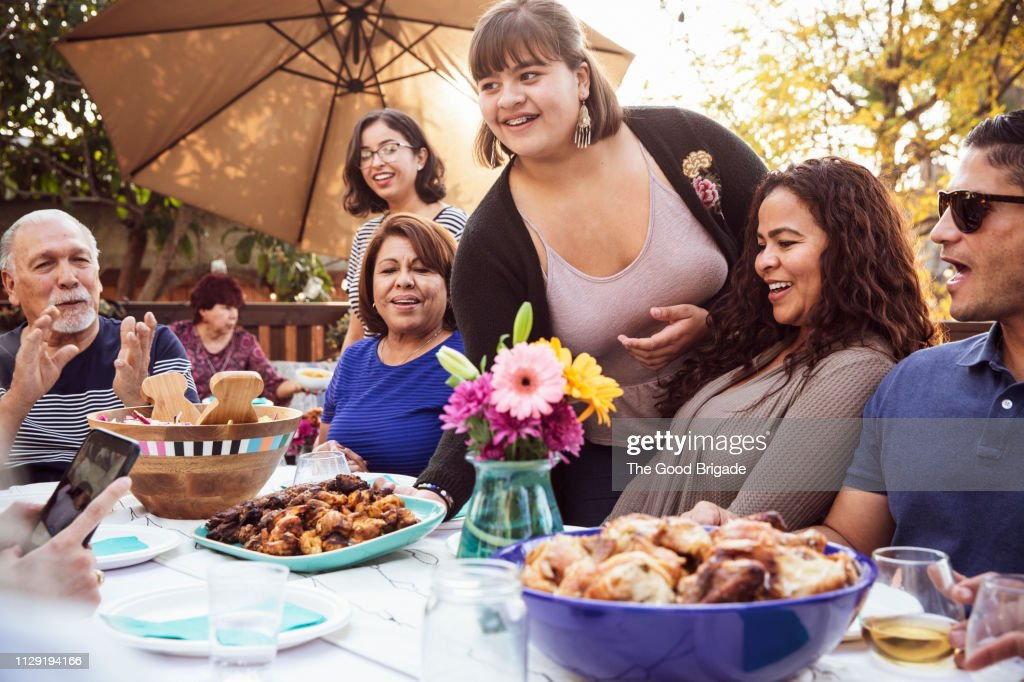 Teenage girl serving food to family at outdoor celebration : Stock Photo