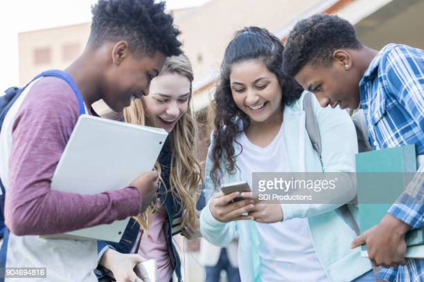 Teenage girl shares funny pictures on smart phone with classmates