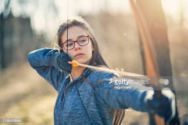 adolescente, un arc de tir - shooting photo photos et images de collection