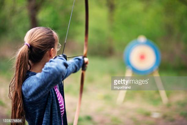 teenage girl shooting bow at target in the forest - sports target stock pictures, royalty-free photos & images