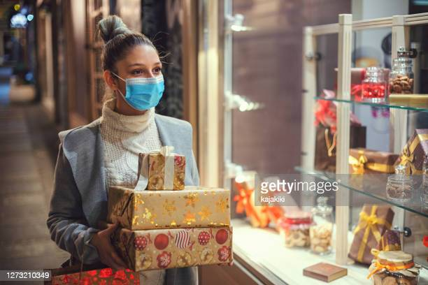 teenage girl shopping christmas gifts during covid-19 pandemic. she wears a protective mask to protect from corona virus covid-19. - coronavirus winter stock pictures, royalty-free photos & images
