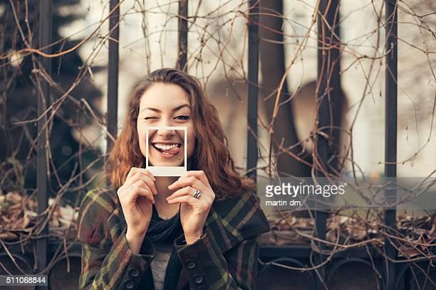 Engraçado Menina adolescente mostrando fotografias instantânea