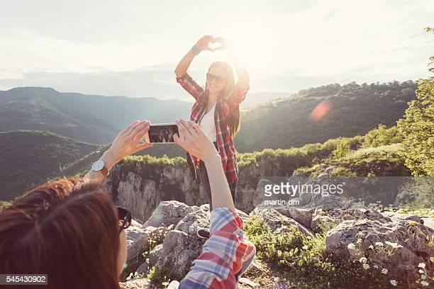 Teenage girl showing heart shaped symbol