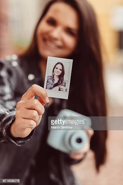 Teenage girl showing instant photo